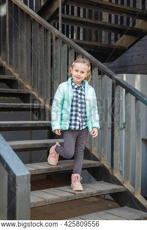 Little Caucasian Blonde Girl In A Fashionable Youth Warm Spring Outerwear Stands On The Iron Vintage