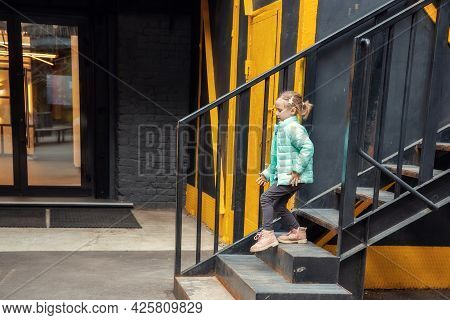 Little Caucasian Blonde Girl In Fashionable Clothes Descends The Metal Steps From The Clothing Showr