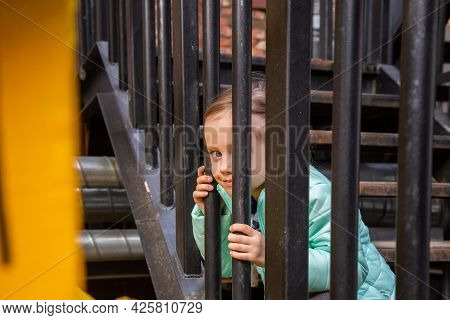 Adorable Little Caucasian Girl Sits On The Iron Staircase With Interest Watching The Passers-by