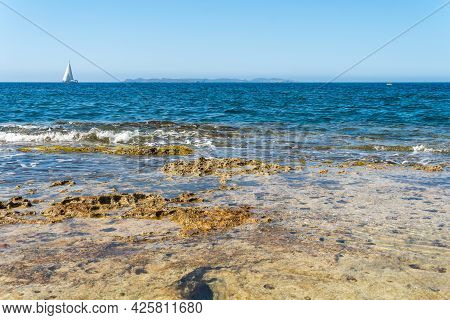 Rocky Coast Of The South Of The Island Of Mallorca At Sunrise With A Sailboat In The Mediterranean S