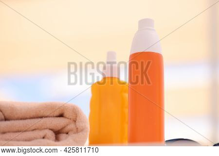 Two Orange Bottles With Sunscreen Lying On Beach Near Towels Closeup