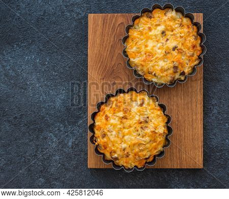 Unsweetened Pies Or Mini Tart With Egg, Chicken, Bell Pepper And Cheese On A Wooden Board On A Black