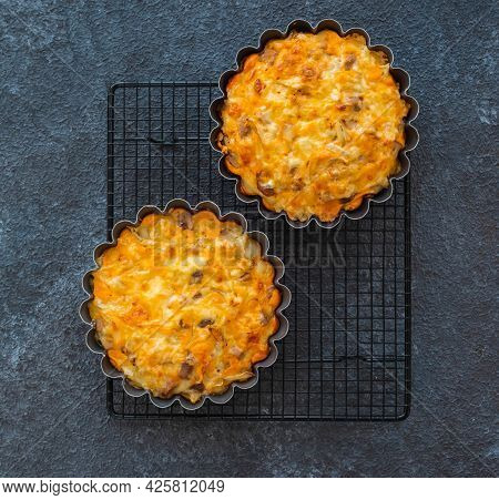 Unsweetened Pies Or Mini Tart With Egg, Chicken, Bell Pepper And Cheese On A Black Wire Rack On A Bl