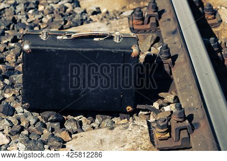 Old Suitcase Stands Near A Rail Of Railroad