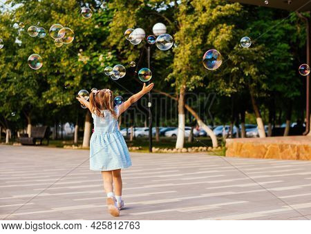 In A Public Park, A Little Girl Blows And Catches Soap Bubbles.the Child Is Playing And Laughing.