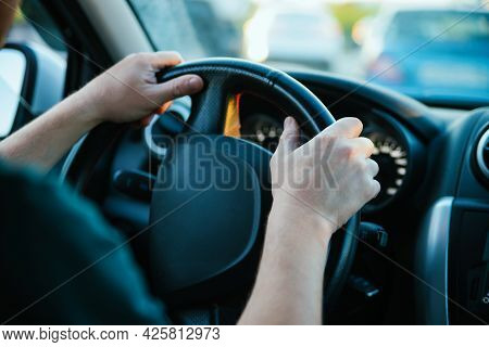 Male Hands Close-up On The Steering Wheel Of A Car. Drive Around The City And Travel.