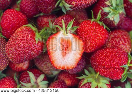 Fresh Strawberries, A Strawberry Berry Is Cut In Half And A Red Juicy Core Is Visible.