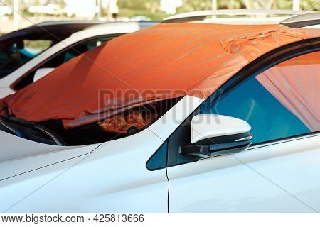 White Car Windshield Covered By Sun Shade Made Of Blanket In Hot Summer Day In Arabian Country