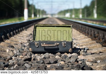 Empty Opened Old Suitcase On The Railroad Sleepers In Summer Morning