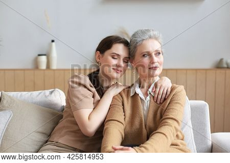 Beautiful Mother And Daughter. Cheerful Young Woman Is Embracing Her Middle Aged Mother In Living Ro