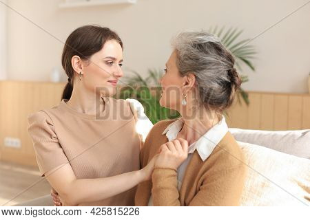 Portrait Of Old Mother And Mature Daughter Hugging At Home. Happy Senior Mom And Adult Daughter Embr