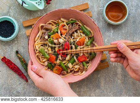 Wok Noodles With Beef, Green Beans And Bell Peppers In A Pink Bowl On A Gray Concrete Background. Ch