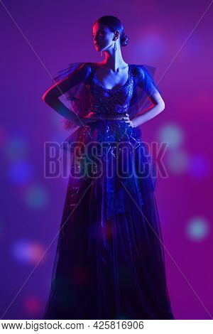 Evening fashion. Full length portrait of a beautiful graceful girl posing in a luxury evening dress in mixed colored light. Studio shot.