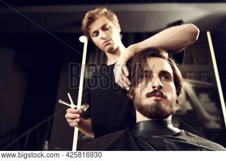 Hairstylist serving client at barbershop. Handsome brunet man visiting hairstylist in hairdressing salon.