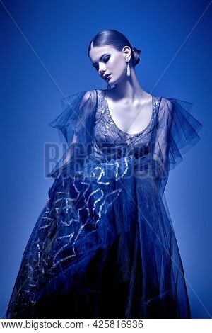 Evening fashion. Beautiful graceful fashion model poses in a luxury evening dress. Studio portrait.