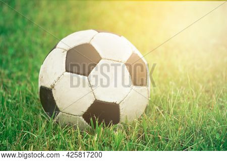 Soccer Ball On Short Green Grass With Sun Rays