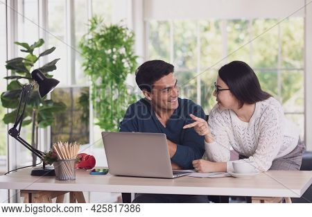 Caucasian Man And Asian Woman Mix Race Lovers Working Together Via Laptop Notebook Computer And Disc