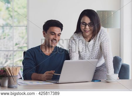 Mixed Races Couple Family, Caucasian Man And Asian Woman, Working Together Via Laptop Notebook Compu