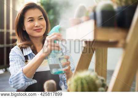 Adult Asian Cute 45s Woman Wearing Apron Holding Sprayer Jug And Spray Droplets Of Water To Cactus I