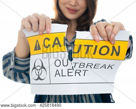Woman Holding And Tearing Paper With Covid-19 Caution Outbreak Alert Words. The Idea Or Concept For