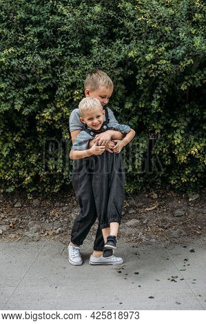 Two Brother Kids Siblings Play Together Near House. Two Little Boys Embrace Brotherly And Having Fun