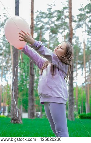 Pretty Girl Tween Teenager In Purple Costume Having Fun Playing With Hot Air Pink Balloon Outdoors.