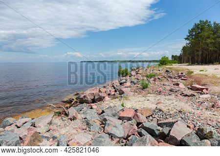 Low Sandy Shore Of Big Reservoir With Stony Shoreline Overgrown With Pine Forest Against The Sky Wit