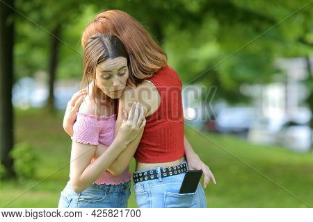 Woman Spying Her Friend Checking Smart Phone Content In A Park
