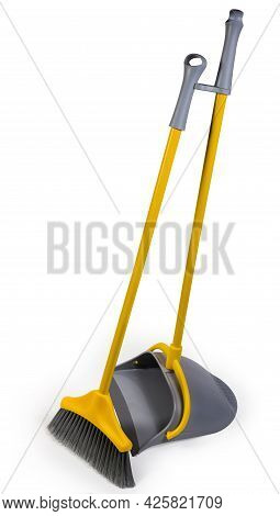 Kit Of The Yellow Long-handled Plastic Broom With Gray Bristles For Sweeping Floors And Dustpan On A