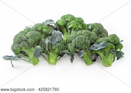Pile Of Small Heads Of Fresh Raw Broccoli On Thick Stalks With Surrounded Leaves On A White Backgrou