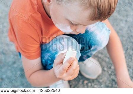 The Child Drawing On The Sidewalk. The Face And Clothes Are Stained With Chalk. Close Up