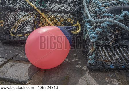Close Up Image Of A Red Buoy Surrounded By Lobster Pots