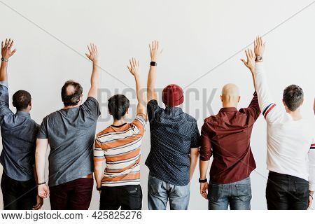 Rearview of business team raising hands