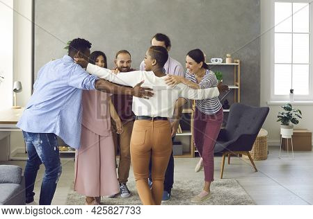 Happy Group Of Young Multinational Friends Greet And Hug During A Meeting At Home.