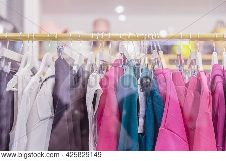 Colorful Clothes On Hangers, Assortment In Clothing Store, Season Sale. Choice Of Clothes In Differe