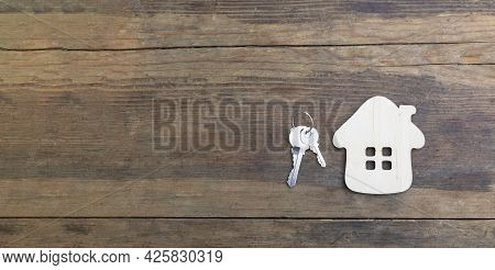 Small House And Keys On An Old Wooden Background. The Concept Of Selling, Buying, Renting Real Estat