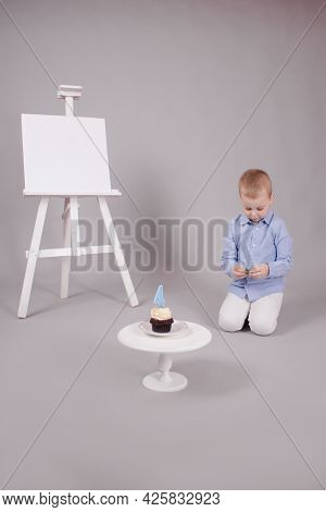 Preschool Boy In White Pants And Blue Shirt On Grey Background Near Easel With Mockup And Cupcake Wi