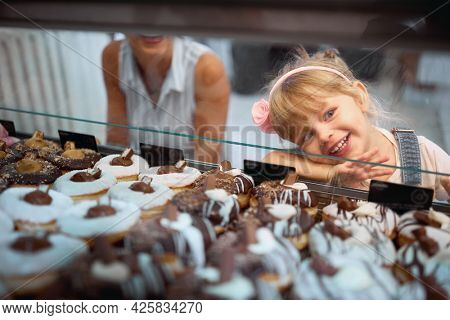 Mother and daughter buying mouth-watering donuts together at store