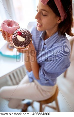 A young attractive girl in a pleasant atmosphere in a pastry shop is amazed and full of desire for delicious donuts she holds in hands. Pastry shop, dessert, sweet