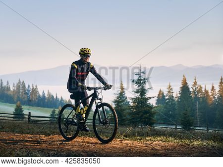 Happy Cyclist In Cycling Suit Riding Bike On Mountain Road With Coniferous Trees And Hills On Backgr