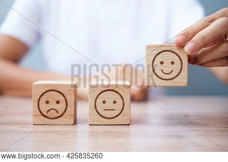 Man Hand Holding Emotion Face Block. Customer Choose Emoticon For User Reviews. Service Rating, Rank