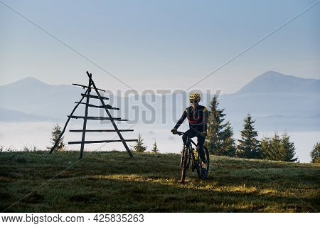 Man In Cycling Suit Riding Bicycle On Grassy Hill In The Morning. Bicyclist In Safety Helmet Enjoyin