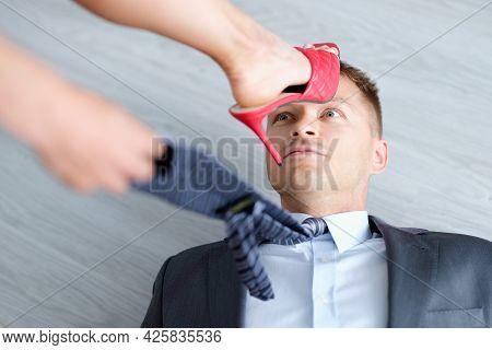 Determined Woman Put Heel On Frightened Man Head