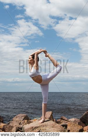 Full Length Of Sportive Woman In Lord Of Dance Pose Near Sea