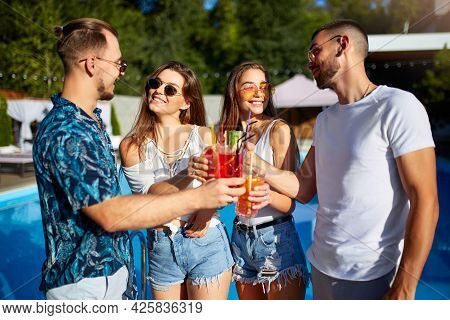 Group Of Friends Having Fun At Poolside Summer Party Clinking Glasses With Summer Cocktails On Sunny