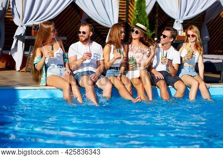 Group Of Friends Having Fun At Poolside Party Clinking Glasses With Fresh Cocktails Sitting By Swimm
