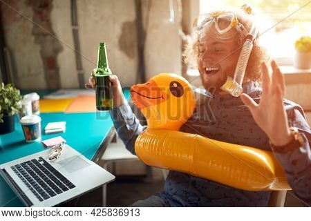 A young man enjoys imagining a beautiful beach while sitting in a relaxed atmosphere in the office with beer and beach accessories