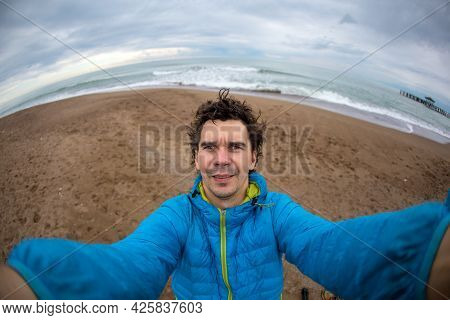 A Man Takes A Selfie Against The Background Of The Sea On A Cold Cloudy Day, A Man Travels Along The
