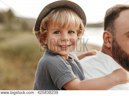 Side View Of Crop Bearded Dad Giving Piggyback Ride To Cute Little Son Smiling And Looking At Camera