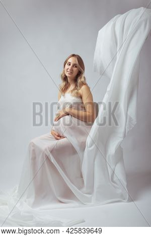 Elegant Pregnant Young Woman Standing Wearing Flying White Fabric. Pregnancy, Maternity And Motherho